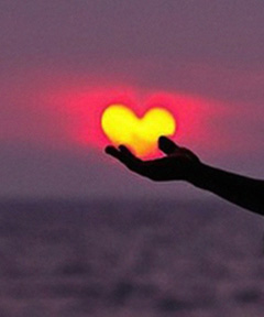Outstretched hand gently supporting a heart-shaped sun.